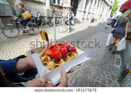 Belgium waffle with chocolate sauce and strawberries, Bruges city background - stock photo