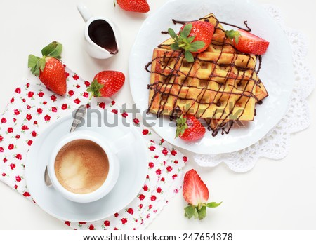 Belgium waffles with strawberries and chocolate decoration on plate with cup of coffee and small jar with chocolate on white table, selective focus - stock photo