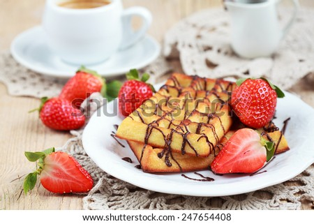 Belgium waffles with strawberries and chocolate decoration on plate with cup of coffee and small jar with chocolate on wooden table, selective focus - stock photo