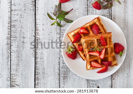 Belgium waffles with strawberries and mint  on white plate. Top view - stock photo