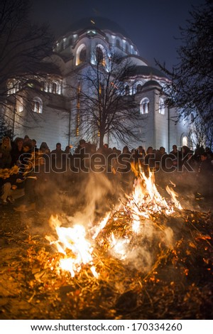 BELGRADE - JANUARY 6: People watch a ceremonial burning of dried oak branches - the Yule log symbol for the Orthodox Christmas Eve in front of St. Sava church on January 6, 2014 in Belgrade, Serbia. - stock photo