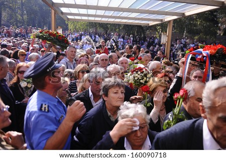 BELGRADE-OCTOBER 26: Serbian police officers hold back Tito supporters following the funeral of his widow, former Yugoslavia's first lady Jovanka Broz, in Belgrade, Serbia on October, 26, 2013 - stock photo