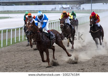 "BELGRADE,SERBIA - APRIL 16: Unidentified horses and jockeys galloping in race ""Tiger heart"" on April 16, 2012 in Belgrade, Serbia - stock photo"
