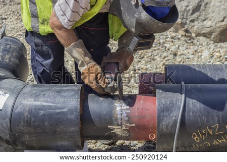 BELGRADE, SERBIA - AUGUST 23: Grinding weld on a pipe segments on the pipeline. At construction site in August 2014. - stock photo