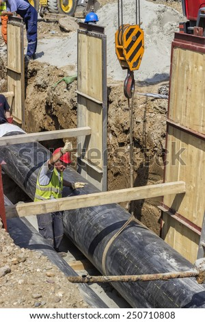 BELGRADE, SERBIA - AUGUST 23: Installing the district heating pipe systems. Laying huge pipe in a trench. At construction site in August 2014. - stock photo