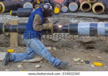 BELGRADE, SERBIA - AUGUST 14: Welder working on pipeline construction. Pipe is supported by crane. Pipe is tack welded. Selective focus. At street Vojvode Stepe in August 2014. - stock photo