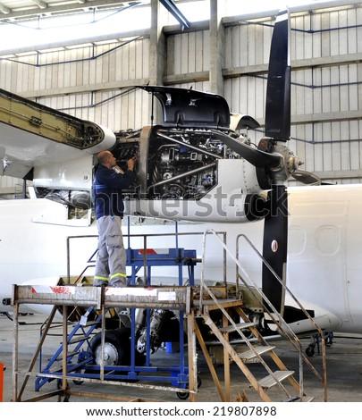 BELGRADE, SERBIA - CIRCA AUGUST 2014: Worker repairs aircraft engine, circa August 2014 in Belgrade - stock photo