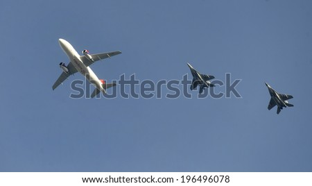 BELGRADE, SERBIA - CIRCA OCTOBER 2013: Air Serbia A-318 flies over escorted with two Serbian Mig-29 fighter jets, circa October 2013 in Belgrade - stock photo