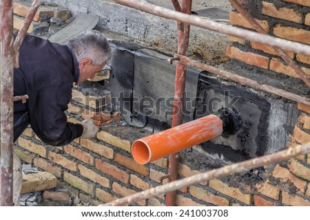 BELGRADE, SERBIA - DECEMBER 26: Pipe through basement wall, outside coated with tar and patched. Basement seal around the waste pipe. Barrier to keep out water. At construction site in December 2014.