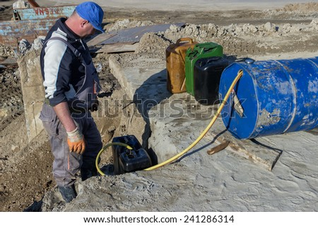 BELGRADE, SERBIA - DECEMBER 25: Worker pouring fuel from barrel into 20 litre plastic fuel containers. At construction site in December 2014.