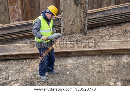 BELGRADE, SERBIA - DECEMBER 15, 2015: Worker with protective equipment cutting metal beams with angle grinder at construction site. Made with selective focus.