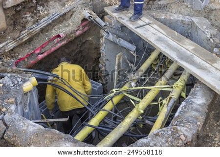 BELGRADE, SERBIA - JANUARY 14: Looking down into hole with electric cables and worker. At construction site in January 2015. - stock photo