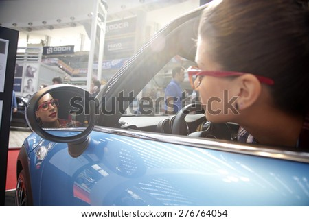 Belgrade, Serbia - March 26, 2015: Hostess posing in blue Mini Moris at Belgrade 52th International Motor Show - MSA OICA