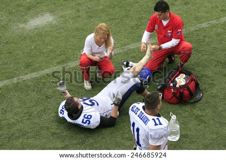 Belgrade, Serbia - May 05, 2014: Doctors tending to injured player. American Football Match Between Belgrade Wolves And Blue Dragon in Belgrade. The Wolves team is winner. - stock photo