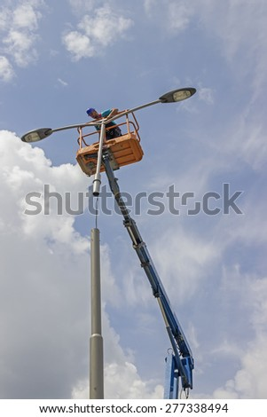 BELGRADE, SERBIA - MAY 10: Worker during installation of metal pole with street lamp, street light. Selective focus. Working on a street reconstruction project in May 2015.