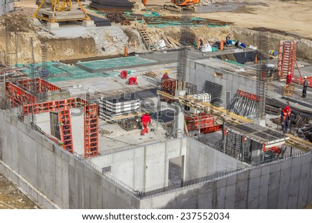 BELGRADE, SERBIA - NOVEMBER 11: Bird view of concrete foundation with reinforcement rods and workers. At construction site in November 2014. - stock photo