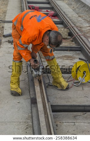 BELGRADE, SERBIA - NOVEMBER 11: Rail worker using angle grinder to grinding tramway track, worker grinding. At street Vojvode Stepe in November 2014.