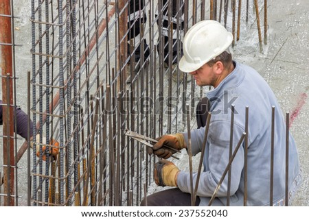 BELGRADE, SERBIA - NOVEMBER 11: Worker working on tying reinforcing steel bars for the construction of a concrete wall. At construction site in November 2014.