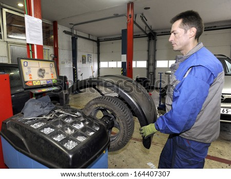 BELGRADE, SERBIA - NOVEMBER 25, 2013: Workers changes tires in car mechanic shop on November 25, 2013 in Belgrade