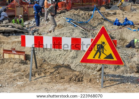 BELGRADE, SERBIA - OCTOBER 01: Traffic sign for construction works in street and workers.  Selective focus. At street Vojvode Stepe in October 2014.
