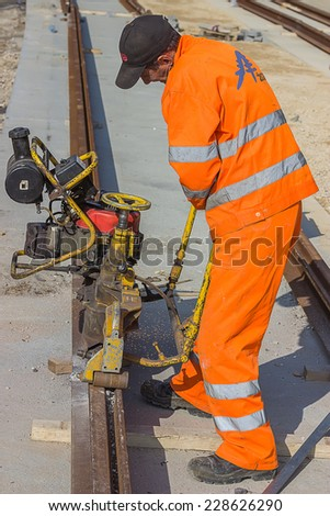 BELGRADE, SERBIA - OCTOBER 29: Tramway track construction worker with rail grinding machine, grinding rail machine. Selective focus. At street Vojvode Stepe in October 2014.