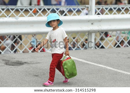 BELGRADE, SERBIA - SEPTEMBER 5 : A small syrian refugee girl in a park full of refugees waiting for the transport to the European Union on September 5th, 2015 in Belgrade, Serbia.  - stock photo