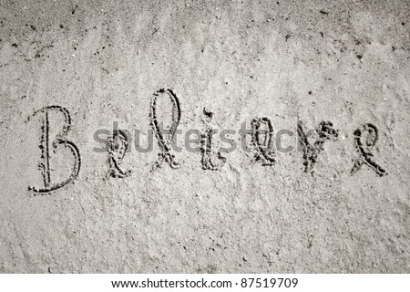 Believe handwritten in sand on a beach