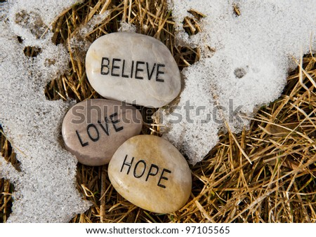 Believe, hope and love rock in the melting snow - stock photo