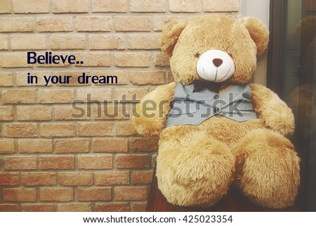 Believe in your dream quote  on blurred brick wall background with vintage filter