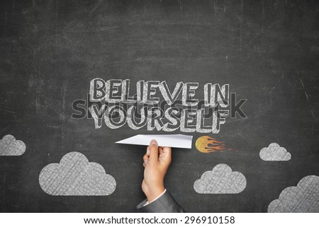 Believe in yourself concept on black blackboard with businessman hand holding paper plane - stock photo