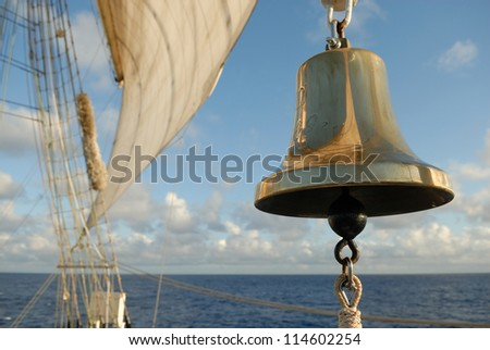 bell and sea sail on the ocean background - stock photo