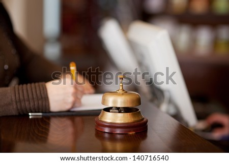 bell at hotel counter with woman filling up a formular - stock photo
