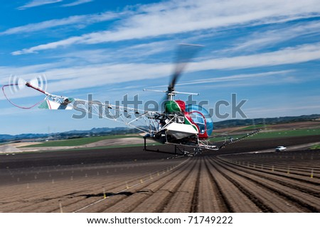 Bell 47 helicopter spraying crops in the Salinas Valley, California - stock photo