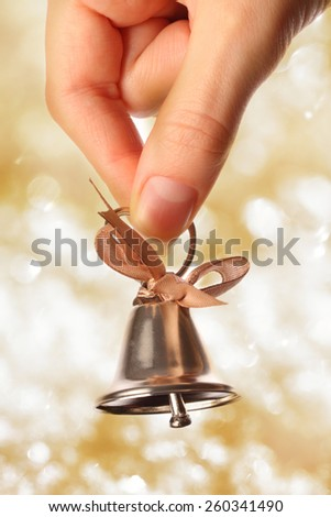 Bell in female hand closeup on sparkle background - stock photo