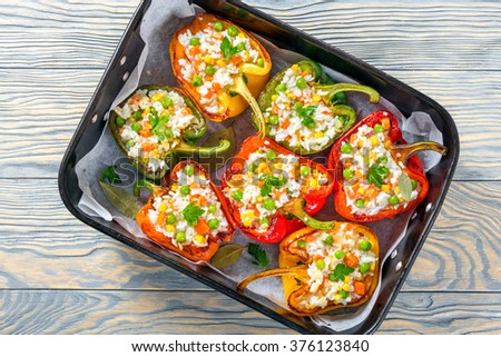 bell pepper cut in half and stuffed with rice, green peas, carrots,Italian seasoning in a baking dish, top view