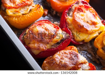 Bell peppers stuffed with chopped meat, cheese and tomato on black baking pan - stock photo