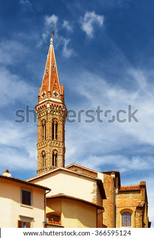 Bell tower of the Badia Fiorentina church at historic center of Florence, Tuscany, Italy. Blue sky in background. Florence is a popular tourist destination of Europe. - stock photo