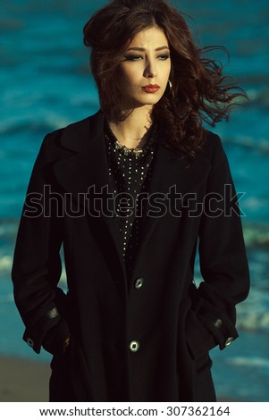 Bella donna concept. Beautiful brunette with long curly hair in black coat. Luxurious golden accessories: earrings, necklace. Perfect make-up. Street & Italian style. Windy weather. Outdoor shot