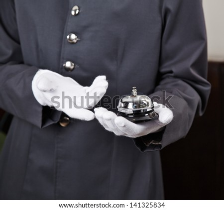 Bellboy holding bell in hotel on his hand - stock photo