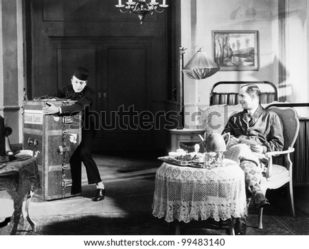 Bellboy struggling with trunk in guests room - stock photo