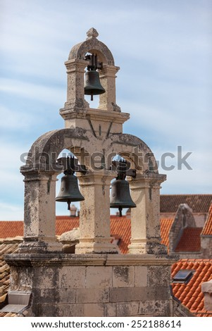 Bellell tower of a church in the old town of Dubrovnik, Croatia with Orange roof tiles houses in the background - stock photo