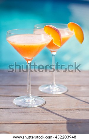 Bellini cocktail with peach isolated near pool