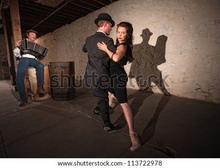 Bellows musician with Tango dancers in spotlight - stock photo