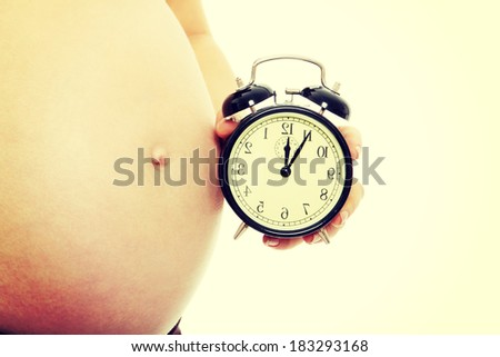 Belly of a pregnant woman with alarm clock, isolated on white