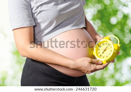 Belly of a pregnant woman with alarm clock on nature background. - stock photo