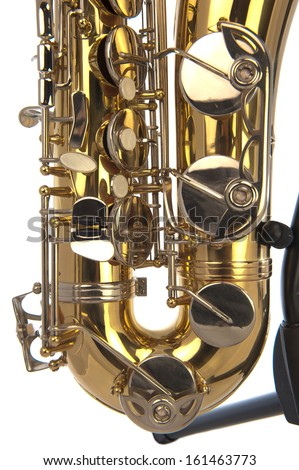 Belly of brass tenor saxophone with silver valves and pearl buttons on a stand in closeup