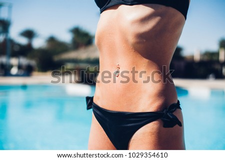 Belly of fit and sexy young woman over sea background. Traveling and vacation concep, black swimsuit, perfect figure, piercing in the belly