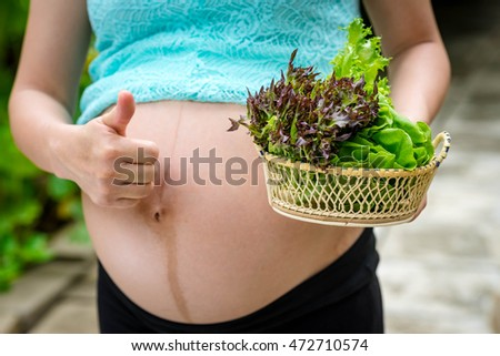 Belly pregnant woman holding vegetable