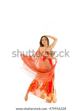 Bellydancer wearing red and brown colored top with skirt, holding veil in hands performing dance, white studio background