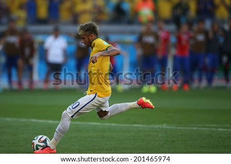 BELO HORIZONTE, BRAZIL - June 28, 2014: Neymar of Brazil kicks a penalty during the 2014 World Cup Round of 16 game between Brazil and Chile at Mineirao Stadium. No Use in Brazil. - stock photo